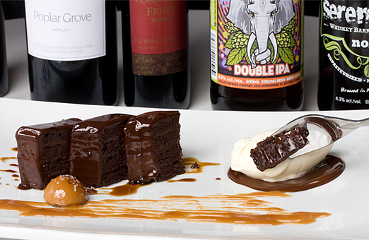 Beer, wine, dessert wines, muscat and port lined up behind Chef Bruno's chocolate torte creation